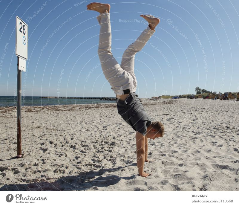 Young man makes handstand at Baltic Sea beach Lifestyle Style Joy Beautiful Athletic Fitness Summer Summer vacation Sun Beach Ocean Track and Field Handstand