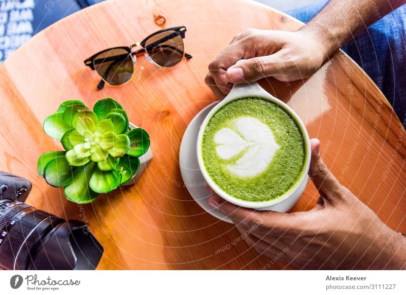 Man holding matcha green tea latte art on a table at a cafe Human being Youth (Young adults) Plant Young man Hand Joy 18 - 30 years Food Lifestyle Adults Wood