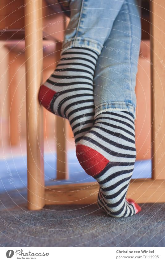 crossed legs with jeans and striped socks Living or residing Flat (apartment) Chair leg table leg Feminine Young woman Youth (Young adults) Legs Feet 1