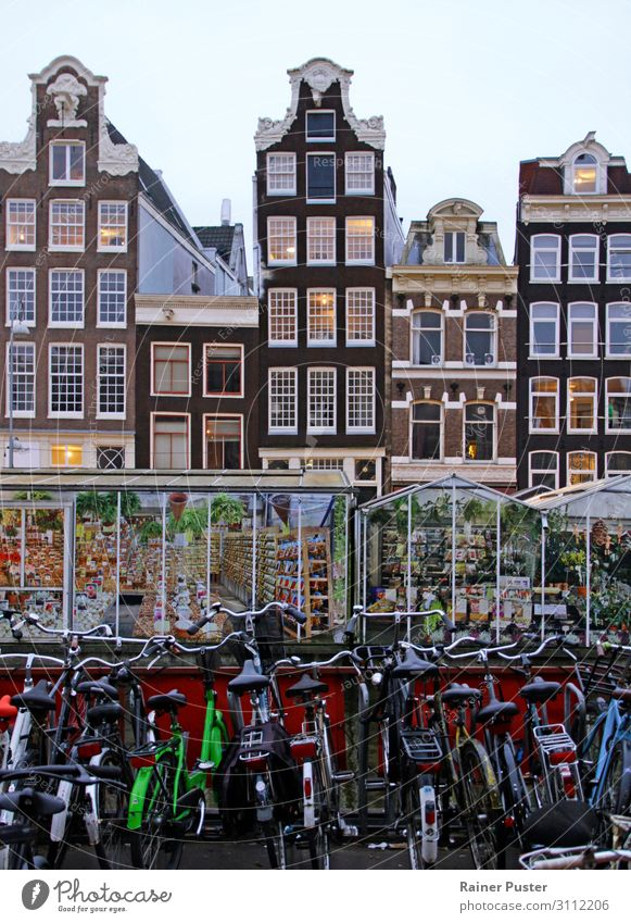 A row of bicycles, behind them greenhouses, behind them the typical narrow buildings of downtown Amsterdam Sightseeing City trip Netherlands Downtown Old town