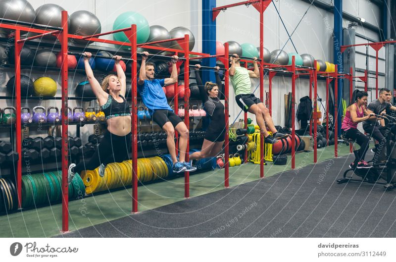 Athletes doing pull ups and air bike in the gym Sports Ball Human being Woman Adults Man Group Fitness Authentic kipping butterfly pull ups cross-training fit