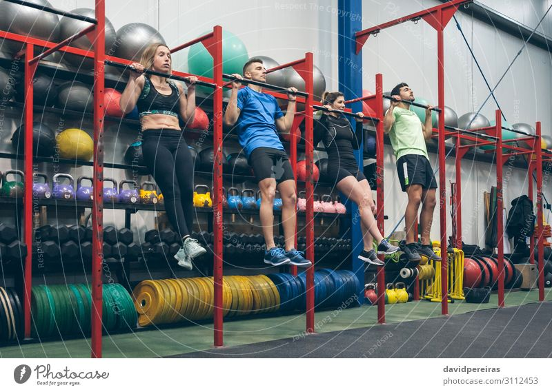 Athletes doing pull ups in the gym Lifestyle Sports Ball Human being Woman Adults Man Group Fitness Authentic Power chin ups rack bar cross fit