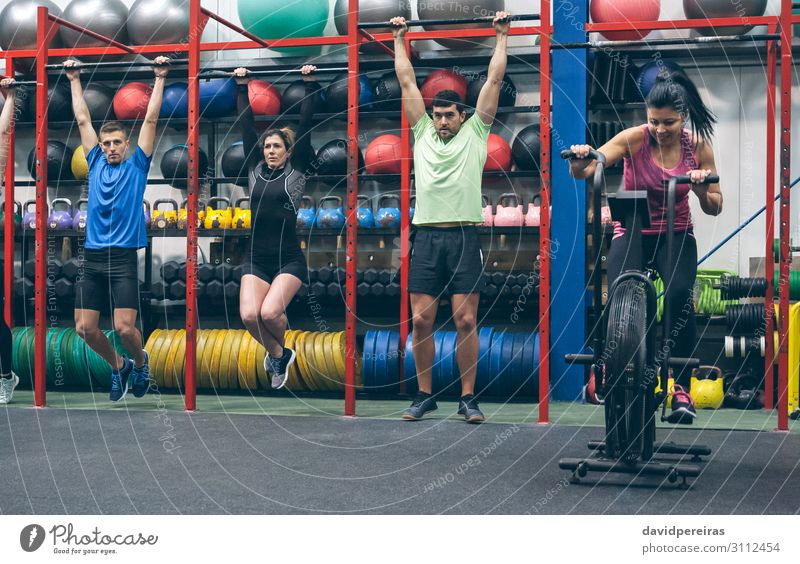 Athletes doing pull ups and air bike in the gym Lifestyle Sports Ball Human being Woman Adults Man Group Fitness Authentic cross-training workout of the day fit