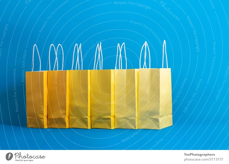Yellow shopping bags on a blue background, Shopping concept Lifestyle Joy Happy Winter Feasts & Celebrations Christmas & Advent New Year's Eve Paper Package