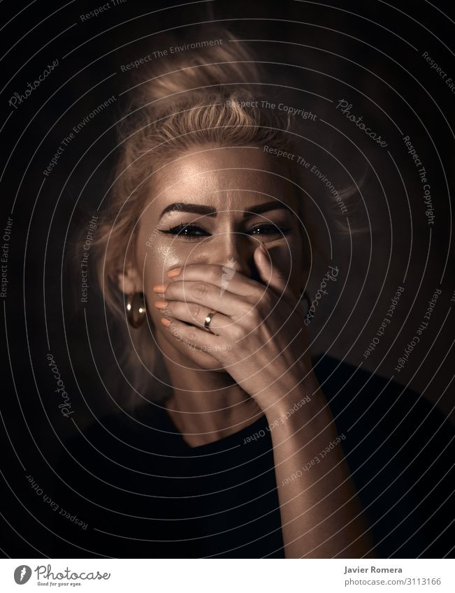 Tousled blonde laughing with her hand covering her mouth Style Beautiful Skin Face Woman Adults Mouth Hand 30 - 45 years Actor Ring Blonde Smiling Laughter