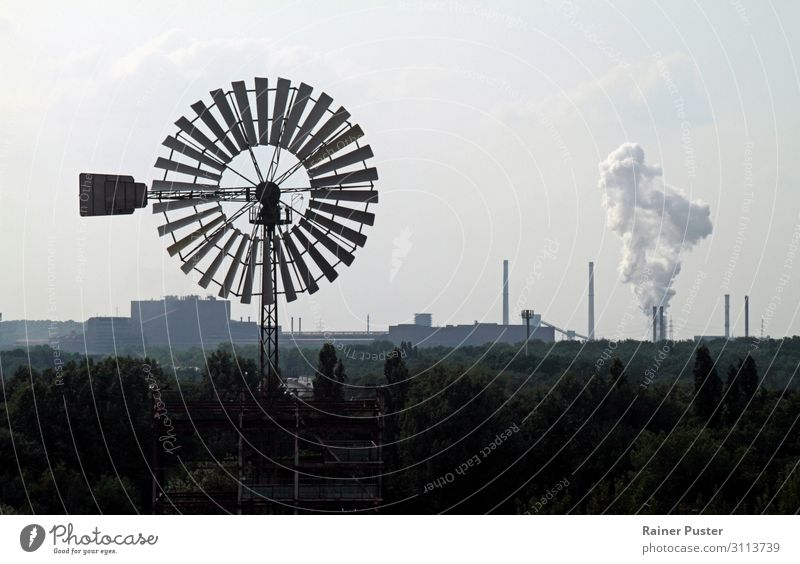 A wind turbine turns in the wind against a background of chimneys and industry. Factory Industry Energy industry Renewable energy Wind energy plant