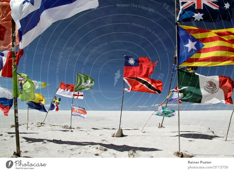 Different flags are waving colourful against the background of the Salar de Uyuni salt desert in Bolivia. Sand Cloudless sky Beautiful weather Wind Desert