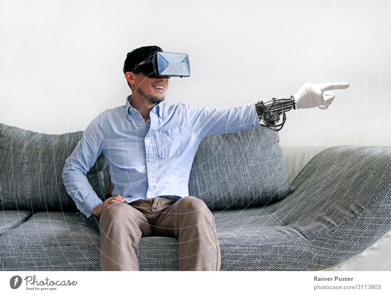 Man on sofa with virtual reality glasses and virtual arm Economy Media industry Telecommunications To talk Headset Computer Hardware VR Glasses Masculine