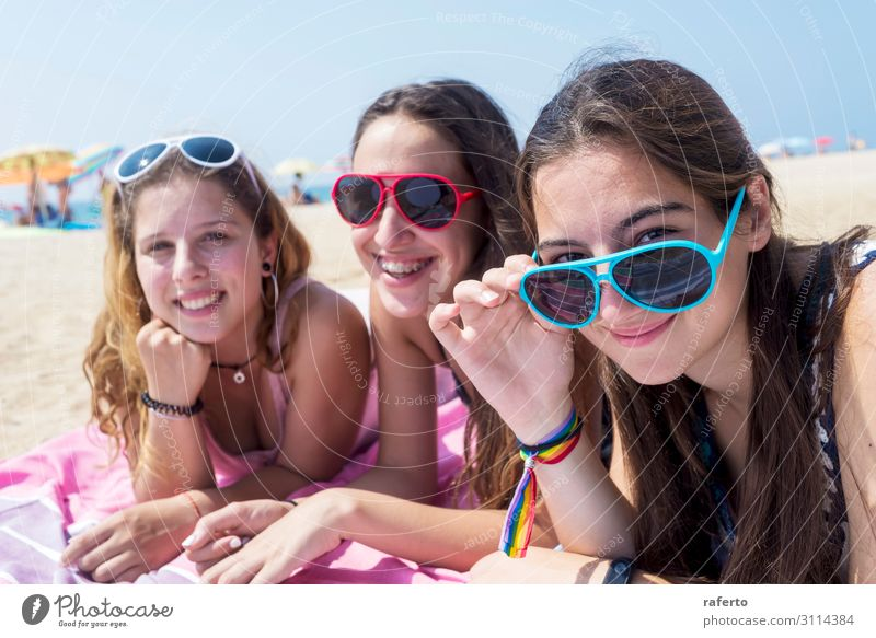 smiling girls best friends lying on beach while looking camera Lifestyle Joy Happy Beautiful Body Face Relaxation Vacation & Travel Summer Beach Ocean