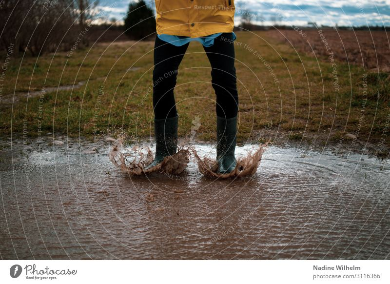 Kid jumping in a puddle Human being Feminine Child Girl Infancy Life Abdomen 1 8 - 13 years Nature Earth Water Clouds Bad weather Rain jacket Rubber boots Jump