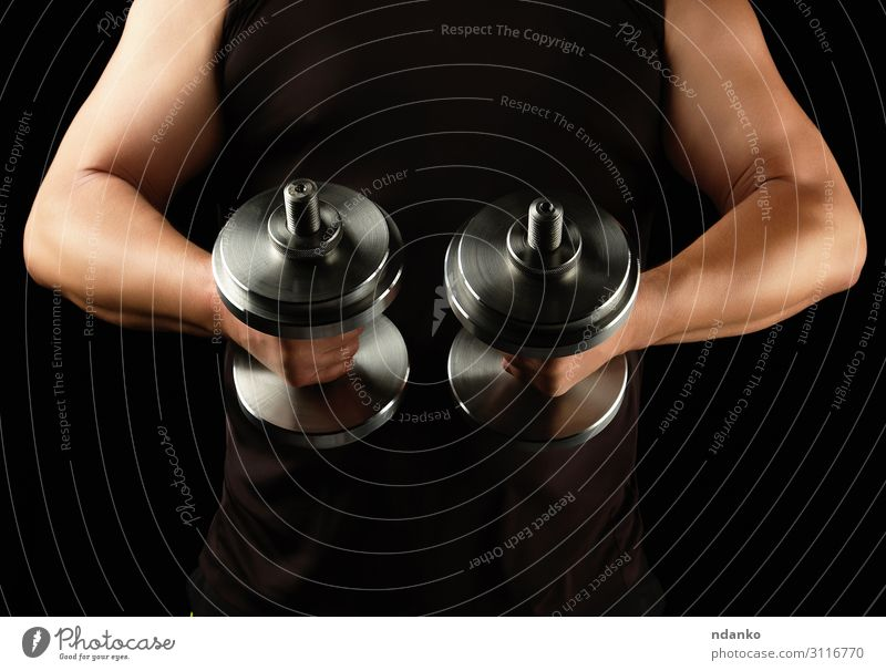 man in black clothes holds steel dumbbells Lifestyle Body Athletic Fitness Sports Human being Man Adults Arm Hand Steel Muscular Strong Black Power abdominal