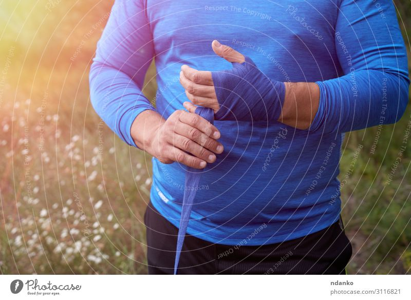 athlete stand and wrap his hands in blue bandage Lifestyle Body Athletic Leisure and hobbies Summer Sports Human being Masculine Man Adults Hand Grass Fitness
