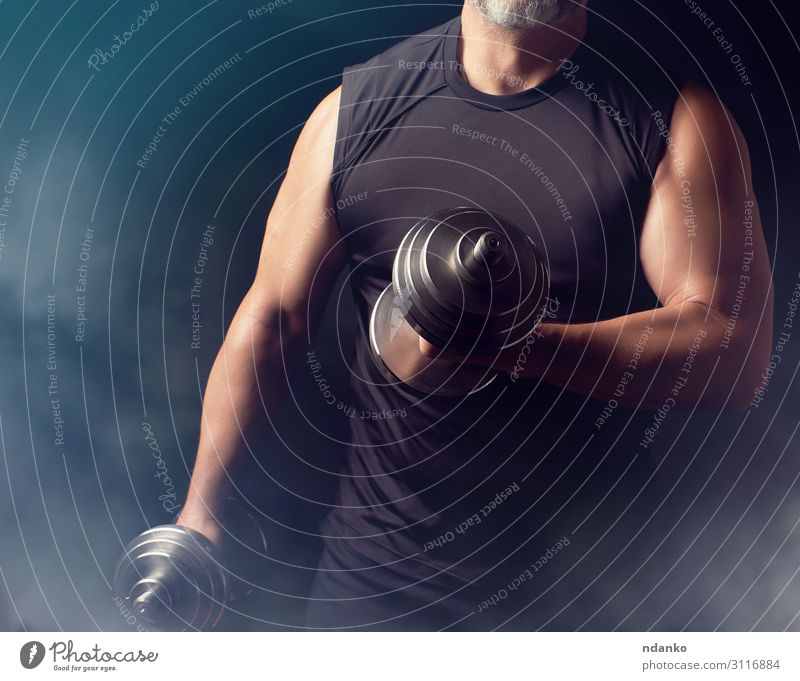man in black clothes holds steel dumbbells Human being Man Hand Black Lifestyle Adults Sports Power Stand Action Fitness Might Athletic Strong Steel Muscular
