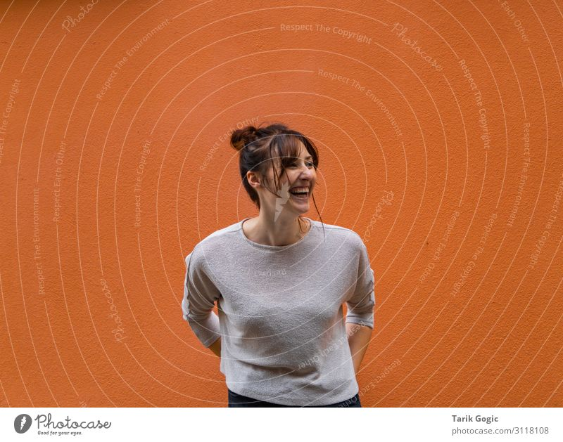 Young laughing woman in front of orange wall Human being Feminine Young woman Youth (Young adults) Woman Adults 1 18 - 30 years smile Laughter Esthetic