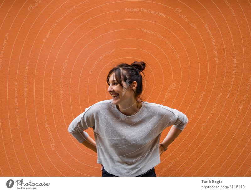 Laughing woman against an orange background Lifestyle Style Joy Happy Leisure and hobbies Human being Feminine Young woman Youth (Young adults) Woman Adults 1