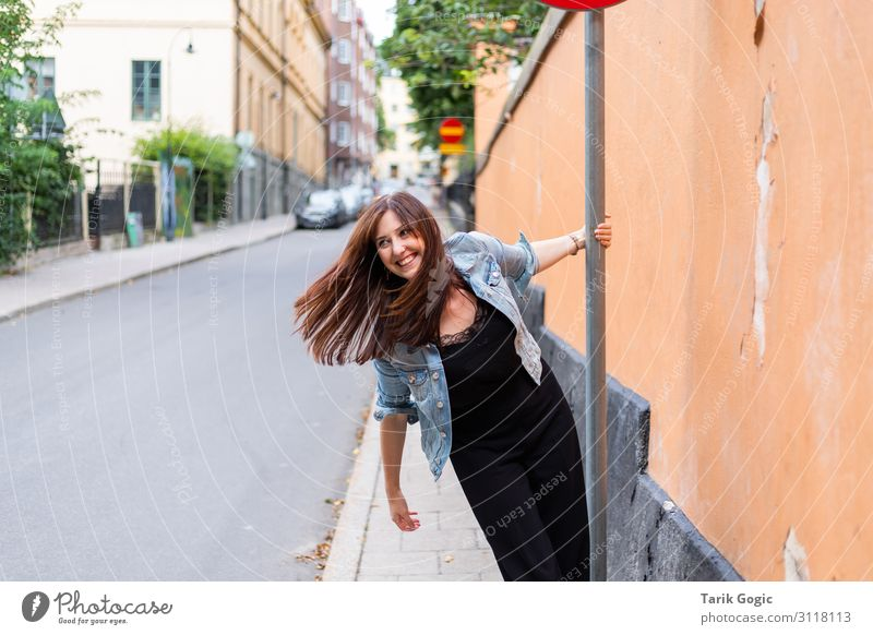 Swinging woman at the street sign Lifestyle Joy Happy Feminine Young woman Youth (Young adults) Woman Adults 1 Human being 18 - 30 years Stockholm Town Downtown