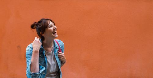 Laughing young woman in front of wall in orange Lifestyle Joy Happy Human being Feminine Young woman Youth (Young adults) Woman Adults Sister 1 18 - 30 years