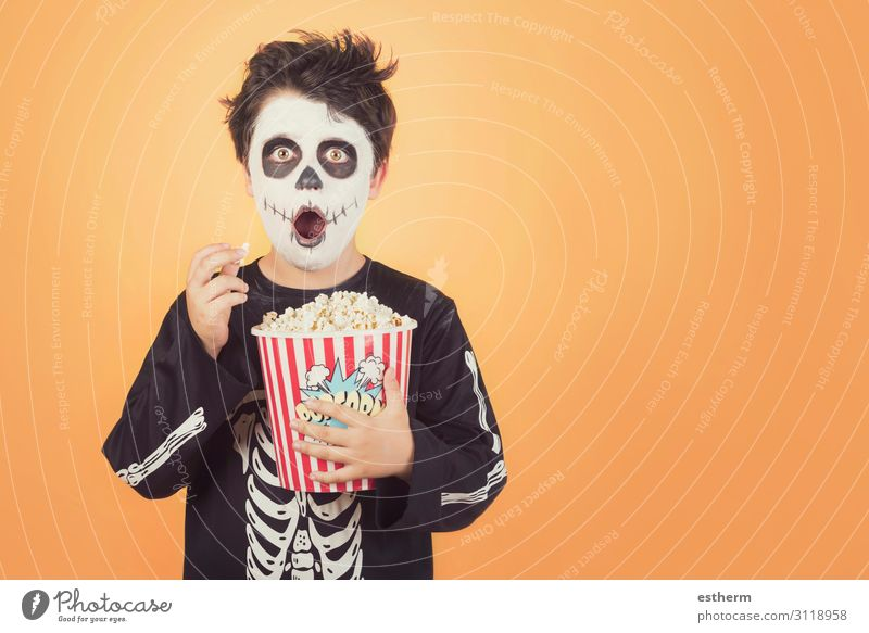 Surprised child in a skeleton costume with popcorn Food Nutrition Eating Medical treatment Entertainment Feasts & Celebrations Hallowe'en Human being Masculine