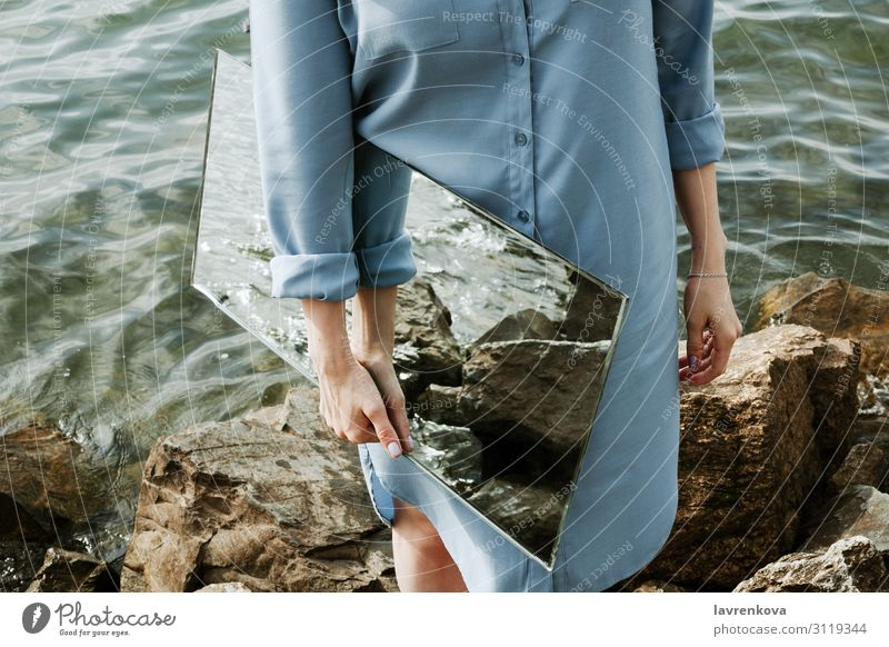 woman standind on a shore in blue dress holding a mirror Environment Clean Nature Conceptual design Adults Rock Waves Horizontal Faceless Dress Coast Reflection