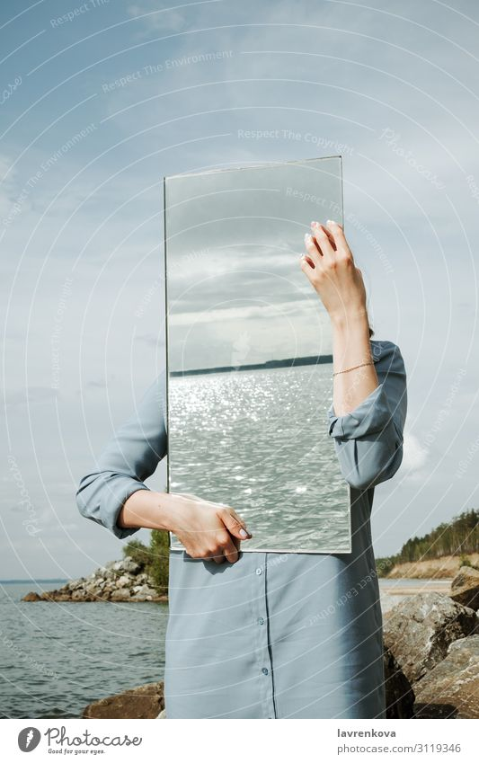 woman standind on a shore in blue dress holding a mirror Adults Clean Conceptual design Dress Environment Faceless Hand Vertical Mirror Nature Exterior shot