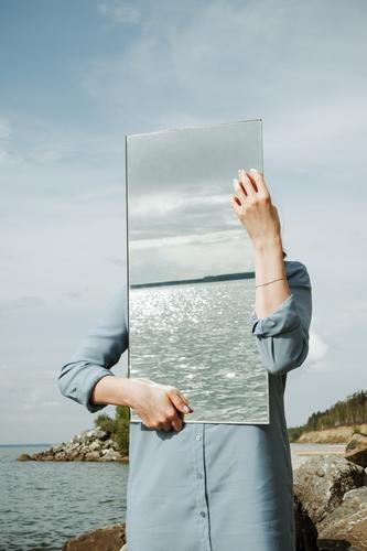 woman standind on a shore in blue dress holding a mirror Nature Water Hand Ocean Adults Environment Coast Rock Waves River Clean Dress Mirror Conceptual design