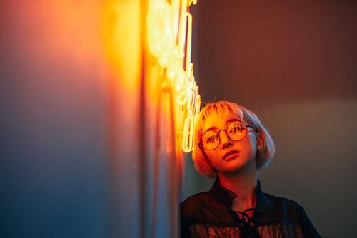 Asian female wearing glasses in front of neon light sign Woman Youth (Young adults) Young woman Red Girl 18 - 30 years Lighting Orange Blonde Eyeglasses