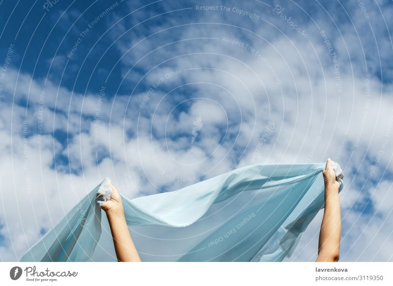 Female hands holding cut of blue cloth up in the sky Horizon Height Story Flying Vantage point Air Hand Exterior shot Summer Nature Loneliness Blue Cloth Clouds