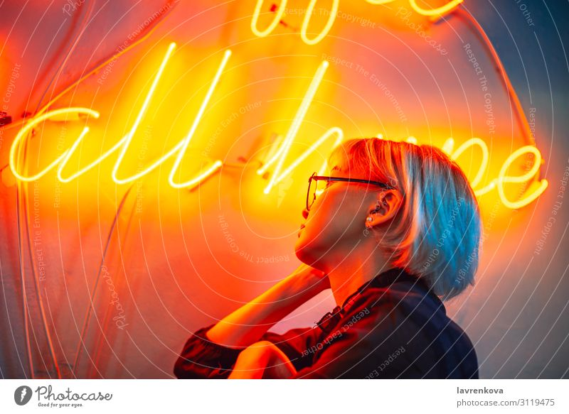 Female wearing glasses in front of neon light sign Asians Blonde Eyeglasses Woman Young woman Girl Lighting Neon light Night life Orange Portrait photograph Red