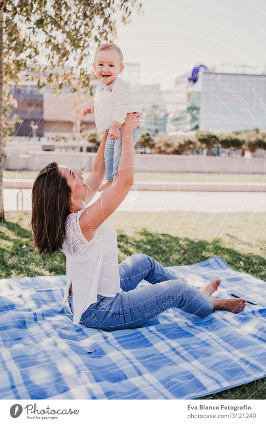 young mother playing with baby girl outdoors in a park Woman Child Human being Nature Youth (Young adults) Young woman Summer Blue Beautiful Green White Sun Joy