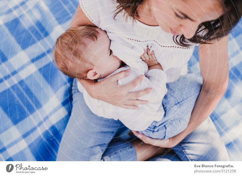 young mother breast feeding her baby girl outdoors in a park Woman Child Human being Nature Youth (Young adults) Young woman Summer Blue Beautiful Green White