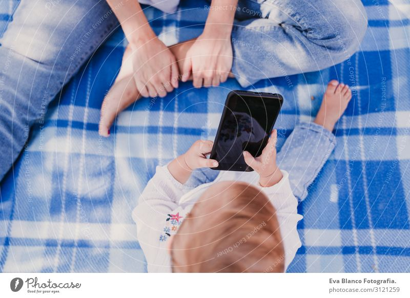 baby girl outdoors in a park using mobile phone Lifestyle Joy Beautiful Playing Summer Sun Parenting Child Cellphone PDA Screen Technology Internet Human being