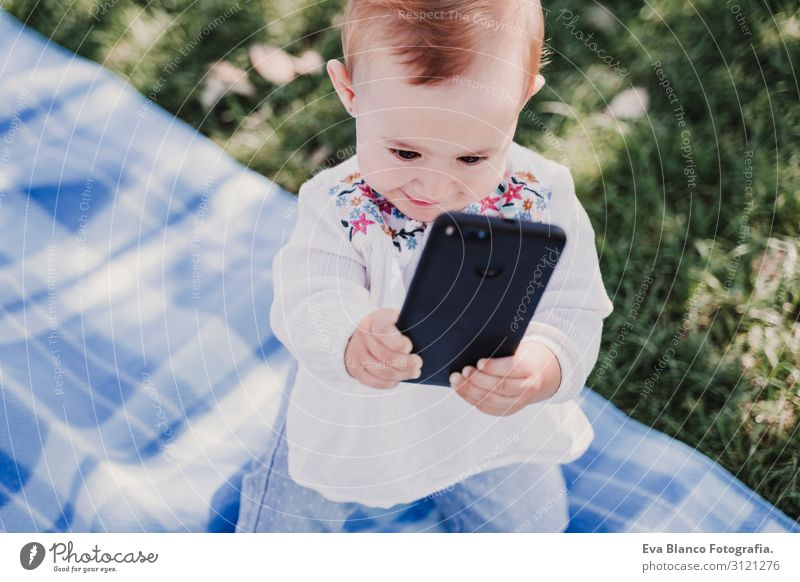 baby girl outdoors in a park using mobile phone Lifestyle Joy Beautiful Playing Summer Sun Parenting Child Cellphone PDA Screen Technology Internet Baby Girl