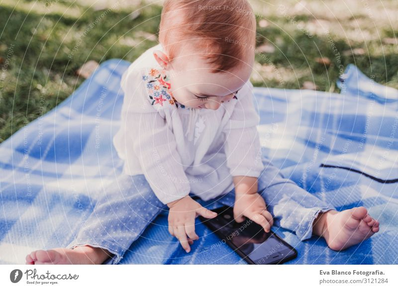 baby girl outdoors in a park using mobile phone Lifestyle Joy Happy Beautiful Playing Summer Sun Parenting Child Cellphone PDA Screen Technology Internet