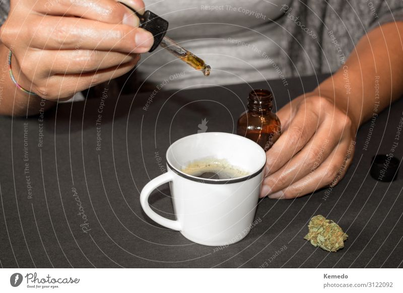 Woman pouring cannabis oil (made with marijuana) in a coffee cup Dessert Herbs and spices Breakfast Beverage Coffee Cup Mug Lifestyle Joy Healthy Health care
