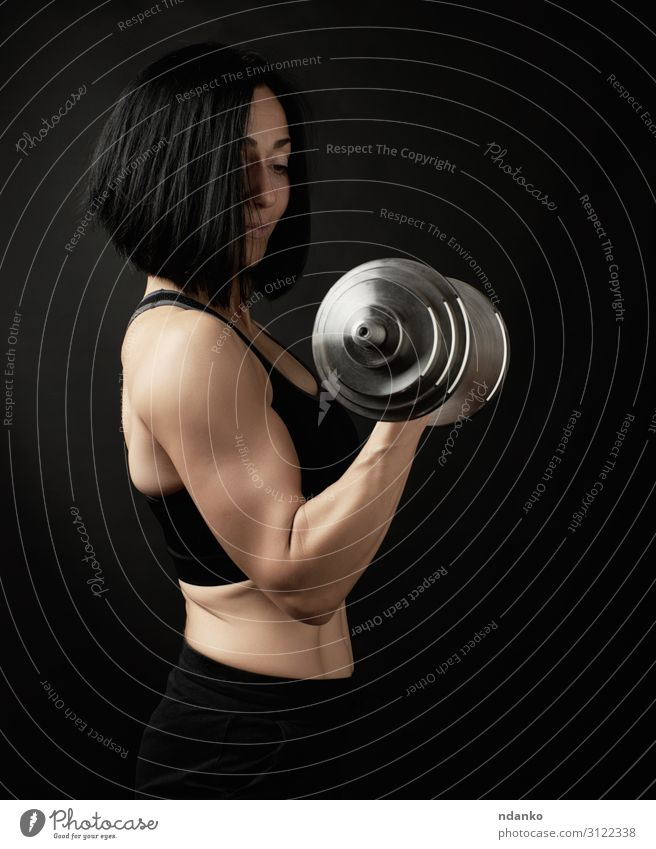 young woman holds steel type-setting dumbbells Woman Human being Hand Black Lifestyle Adults Sports Body Power Action Fitness Energy Athletic Strong Thin