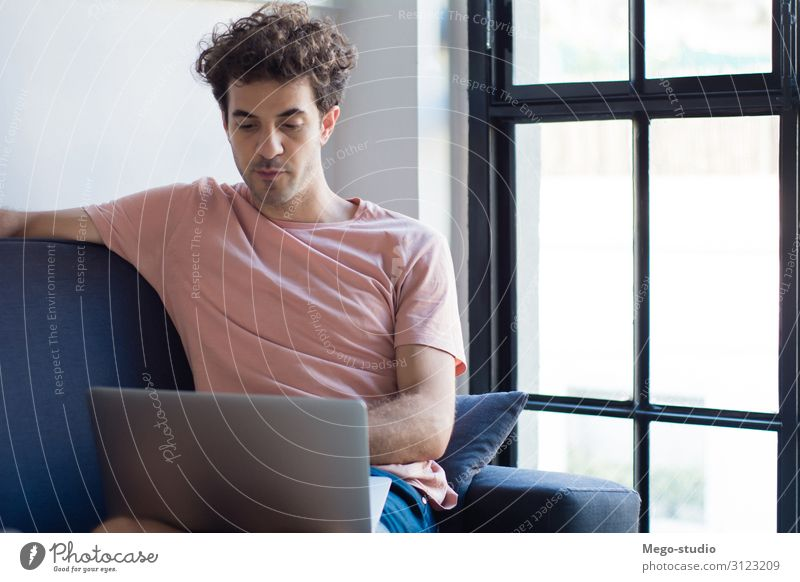 Young man relaxing on the sofa with a laptop Lifestyle Joy Happy Relaxation Calm Leisure and hobbies Reading Flat (apartment) House (Residential Structure) Sofa
