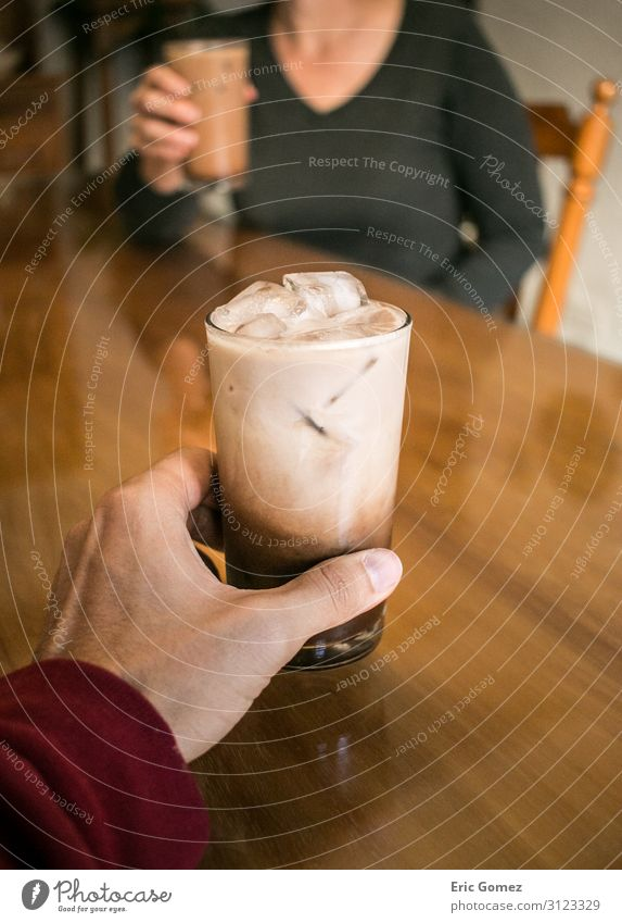 Hand holding coffee, woman drinking in background To have a coffee Drinking Cold drink Milk Espresso Glass Lifestyle Joy Young man Youth (Young adults) Woman