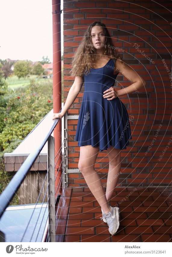Portrait of a young woman on a balcony Lifestyle Style Beautiful Flat (apartment) House (Residential Structure) Balcony Brick Young woman Youth (Young adults)