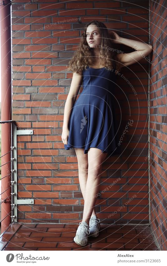 Portrait of a young, tall woman on a balcony with brick wall Lifestyle Style already Flat (apartment) House (Residential Structure) Balcony Brick Young woman