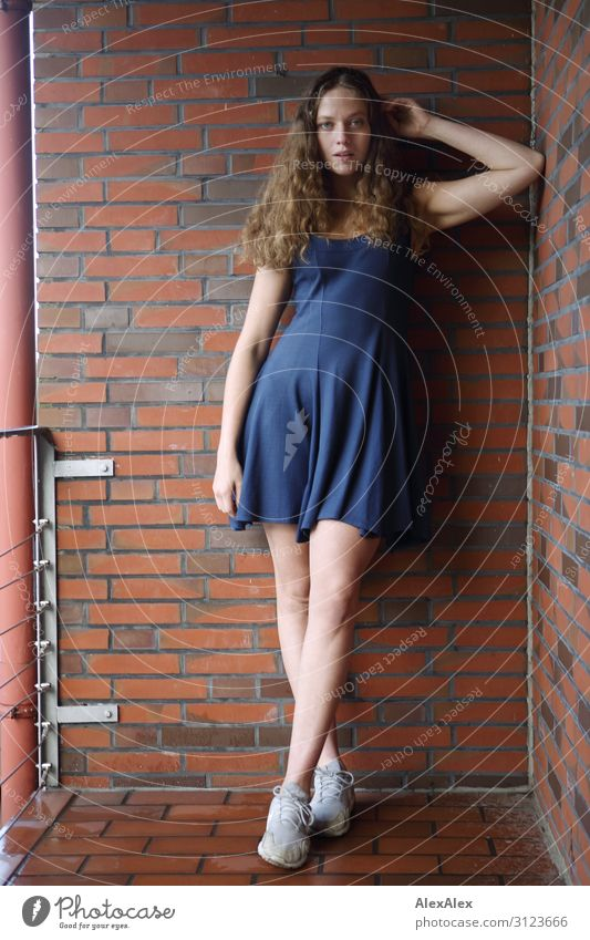 Portrait of a young, tall woman on a balcony with brick wall Lifestyle Style already Flat (apartment) Balcony Brick Young woman Youth (Young adults)