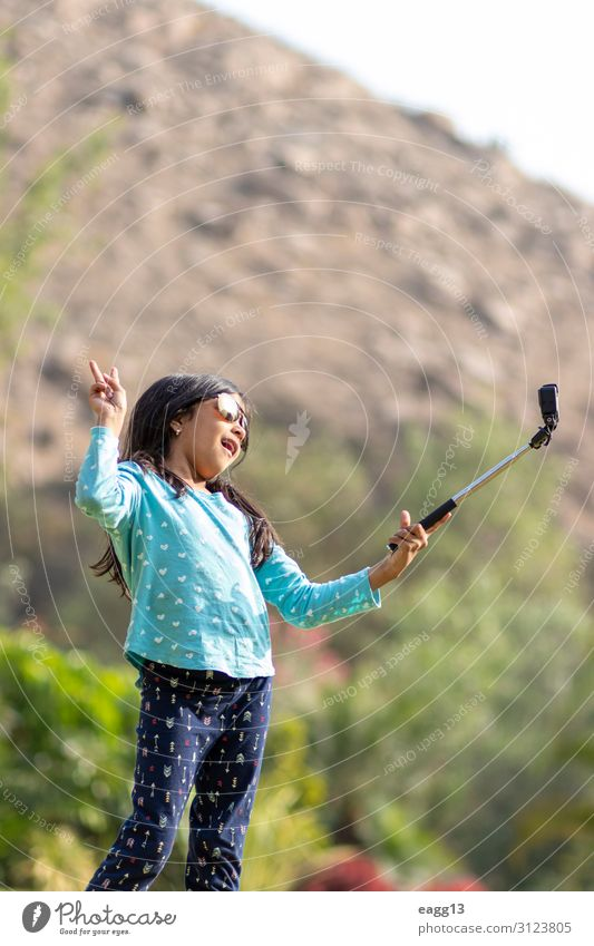 Little girl taking a picture with an action camera Lifestyle Joy Happy Leisure and hobbies Playing Vacation & Travel Child Camera Tool Technology Human being