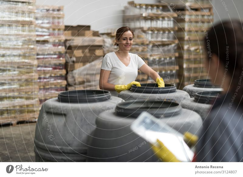 Woman looking tablet in olives warehouse factory controlling fruits fermentation Fruit Work and employment Workplace Factory Industry Business Human being