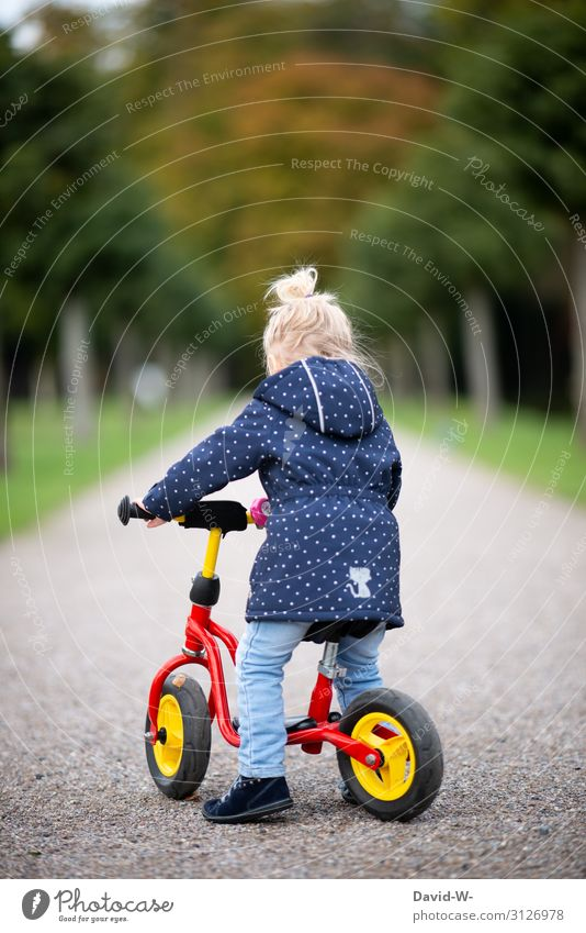 Child rides a bicycle Bicycle Kiddy bike Self-confident Bike helmet Safety Deep depth of field Lanes & trails off Driving Cycling Study
