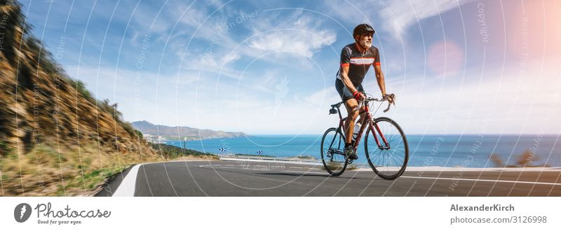 Mature Adult on a racing bike climbing the hill coastal road Vacation & Travel Summer Beach Sports Human being Nature Highway Fitness bicycle cycling sky