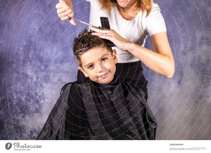 Beautiful boy getting a haircut with scissors Lifestyle Elegant Style Hair and hairstyles Child Work and employment Profession Workplace Business Scissors