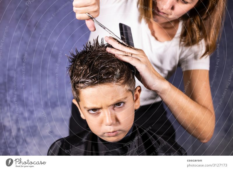 Beautiful boy getting a haircut with scissors Woman Child Human being Blue White Hand Black Face Lifestyle Adults Sadness Style Boy (child) Business Small