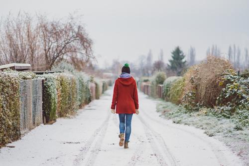 Wide-angle winter landscape with woman in red coat 18 - 30 years Street Winter Loneliness Individual Coat chill Freedom Frozen Garden Jacket Jeans Exterior shot