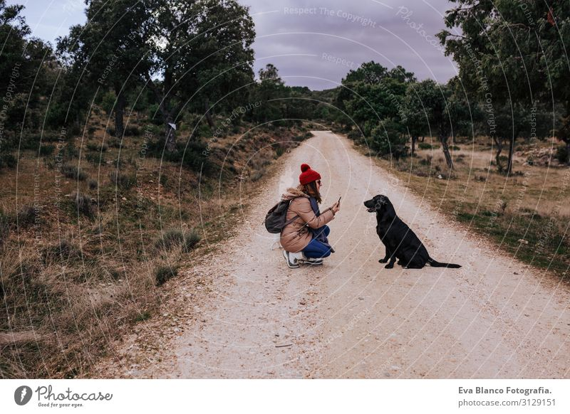 woman using mobile phone outdoors in nature. beautiful black labrador besides. Nature Recklessness Obedient Youth (Young adults) Happy Tongue Green Considerate