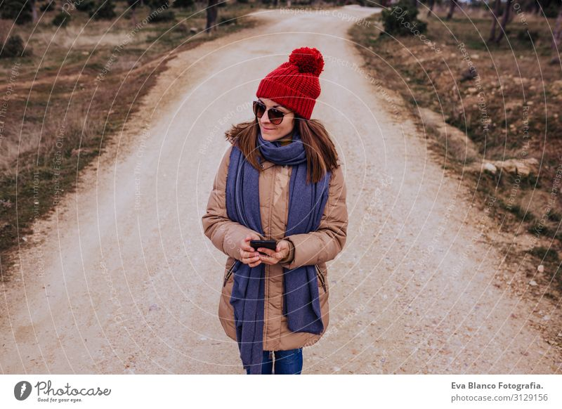 young backpacker woman hiking in nature. Cloudy winter day. Using mobile phone Nature Adventure American discovering traveler Green To enjoy westerner hiker