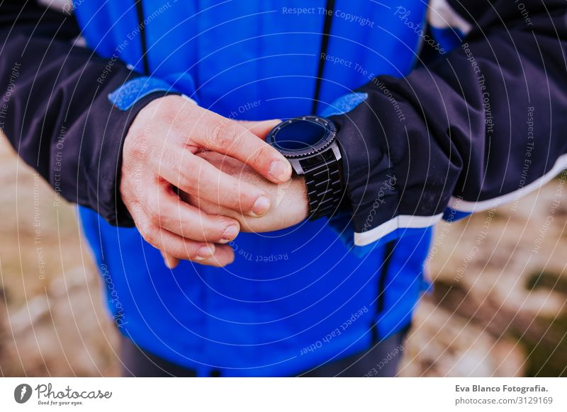 young hiker man checking smart watch on top of the mountain. cloudy day Screen Hiking app ultra Runner workout Fitness Lifestyle Practice device Sports Healthy